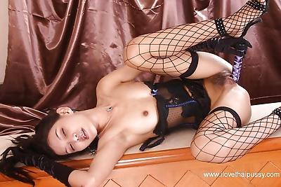 Thai brunette poses in her..