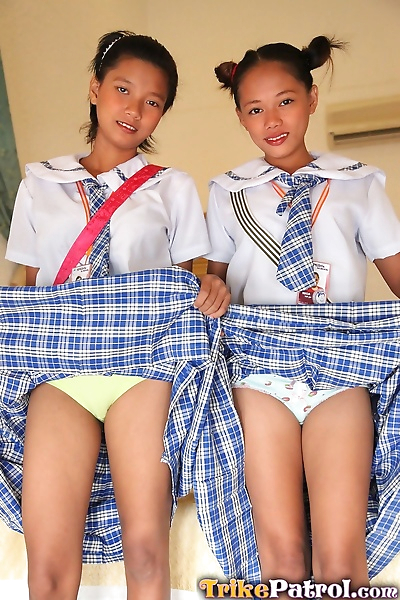 Young Asian schoolgirls lift their uniform skirts to show tiny bare pussy