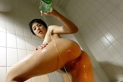 Japanese female Sakura Aida covers herself in oil in the bathtub
